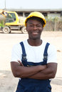 Standing african worker with crossed arms at construction site laughing camera yellow excavator in the background Royalty Free Stock Photography