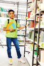 Standing boy with books in school library Royalty Free Stock Photo