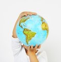 Standing child boy holding a globe in hands in front of his head on white background Royalty Free Stock Images
