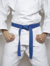 Standing fighter blue belt martial arts white suit Royalty Free Stock Photo