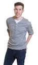 Standing guy in a grey shirt on an isolated white background for cut out Stock Image