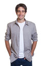 Standing guy in a grey shirt and jeans on an isolated white background for cut out Stock Photos