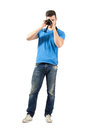 Standing man taking photo with dslr looking at camera young full body length portrait isolated over white background Royalty Free Stock Photos