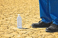 Standing next to desert bottled water a man is a bottle of with it sitting on a playa Royalty Free Stock Images