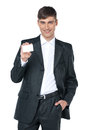 Standing over white background young smiling business man handing a blank business card Royalty Free Stock Photo