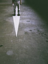 Standing on a painted arrow man an suggesting searching for the true path and reality Stock Photo