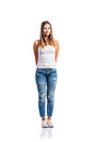 Standing teenage girl in jeans and white singlet,  isolated Royalty Free Stock Photo