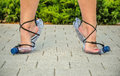 Standing on tiptoe in plastic bottle sandals thrifty woman front view paving stones Stock Image