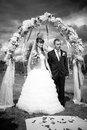 Standing under wedding arch black and white photo of newly married couple Stock Images