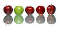 Standout apple a green being among red apples isolated on white background Royalty Free Stock Photography