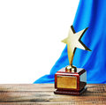 Star award wooden table and on the background of blue curtain Royalty Free Stock Photo