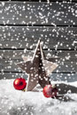 Star decoration red christmas spheres on pile of snow against wooden wall Royalty Free Stock Photo