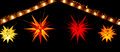 Star gable red yellow and orange morovian stars hang from an illuminated at a christmas market Stock Photo