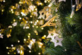 Star hanging on christmas tree with bokeh light in green yellow golden color, holiday abstract background, blur defocused Royalty Free Stock Photo