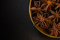 Star shape anis seeds in bowl on black slate Royalty Free Stock Photo