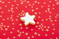Star shaped cinnamon biscuit on red background with golden stars Stock Images