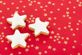 Star shaped cinnamon biscuits on red background with golden stars Royalty Free Stock Photo