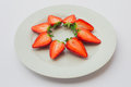 Star shaped decoration of fresh halved strawberries on a white plate. Royalty Free Stock Photo
