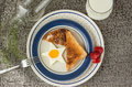 Star shaped fried egg and toast with strawberries on the side sitting in a white plate with a blue rim Royalty Free Stock Photo