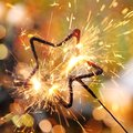Star sparkler close up of holiday and defocused lights on background Royalty Free Stock Photography