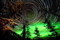 Star trails and Northern lights in sky over taiga Royalty Free Stock Photo