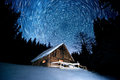 Star trails over wooden house in the winter forest Royalty Free Stock Photo
