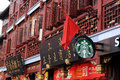 A starbucks logo is seen hanging on a traditional chinese building under a red chinese national flag along with other chinese Stock Photos