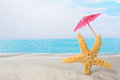 Starfish on beach with parasol Royalty Free Stock Photo