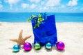 Starfish with Christmas balls and gift bag on the beach Royalty Free Stock Photo