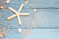 Starfish and fishing net on blue boards Royalty Free Stock Photo