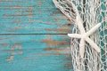 Starfish in a fishing net with a turquoise wooden background sha shabby style Stock Photography
