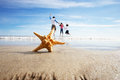 Starfish in foreground as father plays with children in sea background Royalty Free Stock Photography