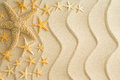 Starfish on golden beach sand with wavy lines scattered dried in different sizes arranged to the left side decorative in a Royalty Free Stock Photo