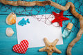 Starfish, pebbles and shells lying on a blue wooden background with postcard. There is a place for labels.
