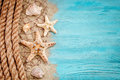 Starfish, pebbles and shells lying on a blue wooden background . There is a place for labels.