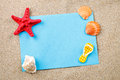 Starfish, pebbles and shells lying on the sand on the postcard.