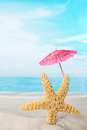 Starfish with pink parasol Royalty Free Stock Photo