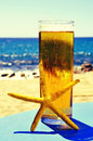 Starfish and refreshing beer on the beach Royalty Free Stock Photo