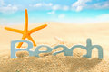Starfish and sign for beach in sea sand colourful orange standing upright behind a golden on the seashore of an idyllic tropical Royalty Free Stock Photos