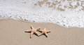 Starfishes on the sandy beach two by ocean s wave Royalty Free Stock Images