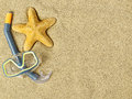 Starfishes and swimming goggles on sand Royalty Free Stock Photo
