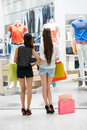 Staring at shopping window young ladies with bags looking a shop viewed back Stock Image