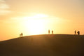 Staring at the sun small group of people on top of sand dune straight blinding Stock Images