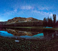 Starry sky reflection at a mountain lake. Royalty Free Stock Photo