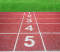 Start or finish position on running track with green field Royalty Free Stock Photo