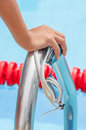 Start swimming race concept with closeup the hand grab on ladder bar goggles Royalty Free Stock Photo