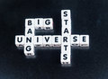 Start of universe text big bang starts inscribed in black uppercase letters on small white cubes crossword style dark background Stock Images