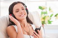 Starting day with her favorite music happy young woman in headphones listening to mp player and smiling Stock Image