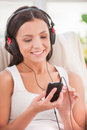 Starting day with her favorite music happy young woman in headphones listening to mp player and smiling Stock Photography