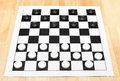 Starting position on vinyl checkers board x wooden table Stock Images
